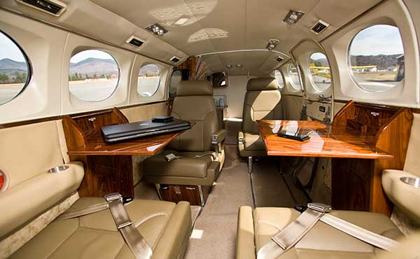 Roomy cabin with leather seats and two wood tables in Adirondack Flying Service Cessna 421