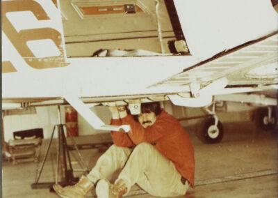 An aircraft maintenance man under aircraft in the 1970's