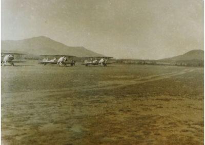 3 vintage biplanes on the dirt runway